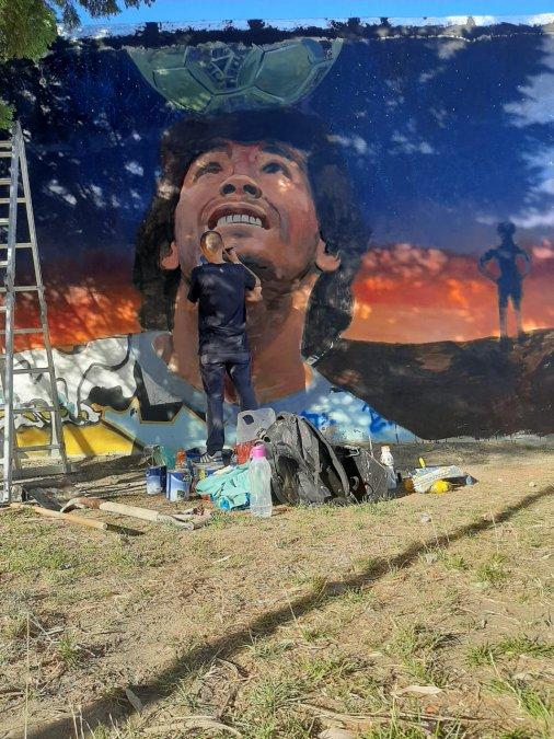 El artista Cristian English trabajando en el mural de Diego Maradona en el barrio 13 de Diciembre.